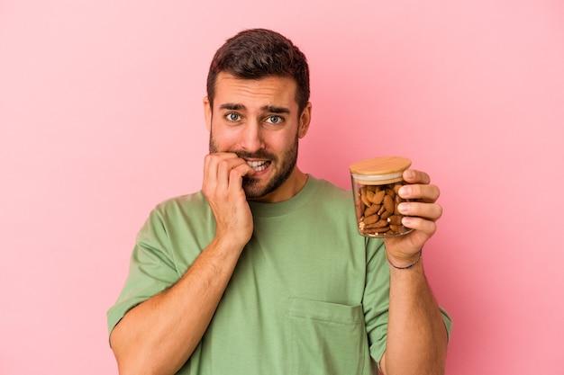 Jovem homem caucasiano segurando um frasco de amêndoa isolado no fundo rosa, roendo as unhas, nervoso e muito ansioso.