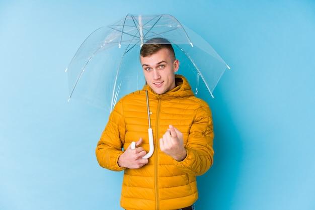 Jovem homem caucasiano segurando um guarda-chuva apontando com o dedo para você como se estivesse convidando se aproximar.