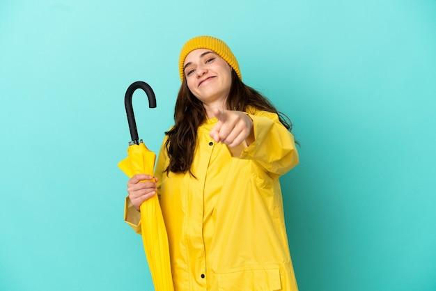 Jovem homem caucasiano segurando um guarda-chuva isolado em um fundo azul apontando para a frente com uma expressão feliz