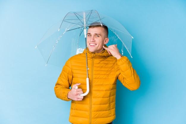 Jovem homem caucasiano segurando um guarda-chuva, mostrando um gesto de chamada de telefone móvel com os dedos.