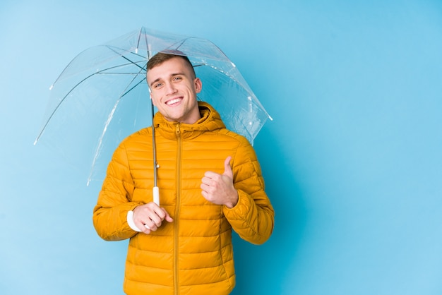 Jovem homem caucasiano segurando um guarda-chuva, sorrindo e levantando o polegar
