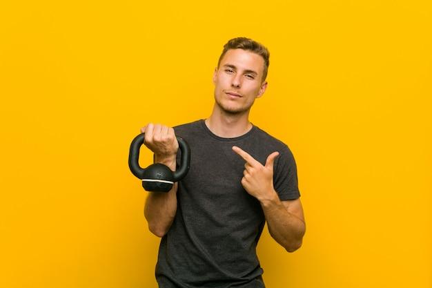 Jovem homem caucasiano segurando um haltere apontando com o dedo para você como se estivesse convidando se aproximar.