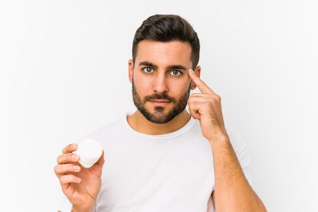 Jovem homem caucasiano segurando um hidratante isolado apontando sua têmpora com o dedo, pensando, focado em uma tarefa.
