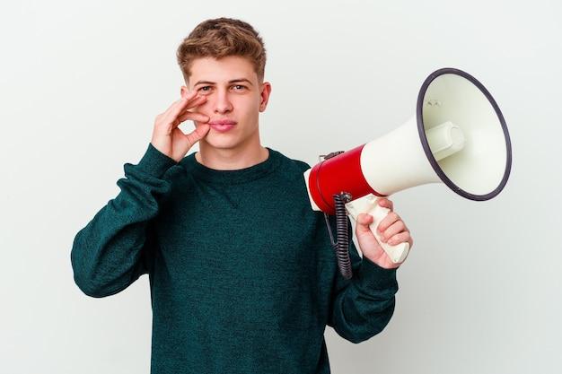 Jovem homem caucasiano segurando um megafone isolado na parede branca com os dedos nos lábios, mantendo um segredo.