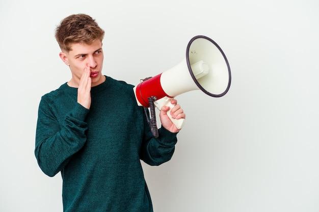 Jovem homem caucasiano segurando um megafone isolado na parede branca está contando uma notícia secreta sobre a travagem e olhando para o lado
