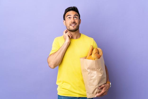 Jovem homem caucasiano segurando um saco cheio de pães, isolado na parede roxa, pensando em uma ideia