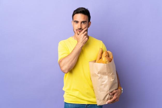 Jovem homem caucasiano segurando um saco cheio de pães isolado na parede roxa, pensando uma ideia