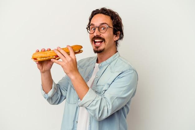 Jovem homem caucasiano segurando um sanduíche isolado no fundo branco