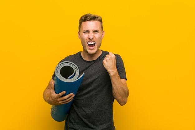 Jovem homem caucasiano segurando um tapete torcendo despreocupado e animado. conceito de vitória
