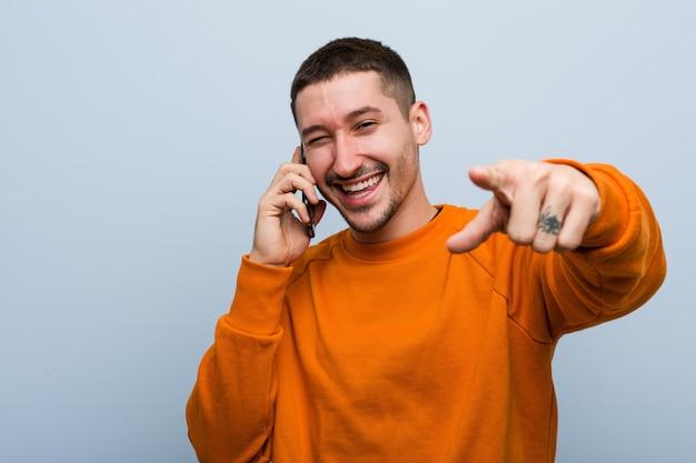 Jovem homem caucasiano segurando um telefone alegre sorrisos apontando para a frente.