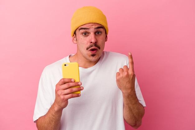Jovem homem caucasiano segurando um telefone celular isolado no fundo rosa, tendo uma ótima ideia, o conceito de criatividade.