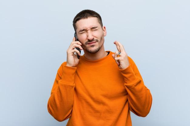 Jovem homem caucasiano segurando um telefone cruzando os dedos por ter sorte