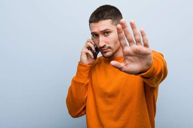 Jovem homem caucasiano segurando um telefone em pé com a mão estendida, mostrando o sinal de stop, impedindo-o.
