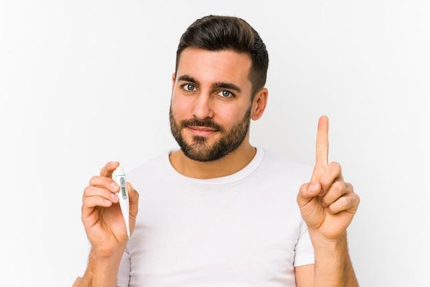 Jovem homem caucasiano segurando um termômetro isolado jovem homem caucasiano segurando uma exibição número um com o dedo.