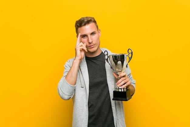 Jovem homem caucasiano segurando um troféu, apontando sua têmpora com o dedo, pensando, focado na tarefa.