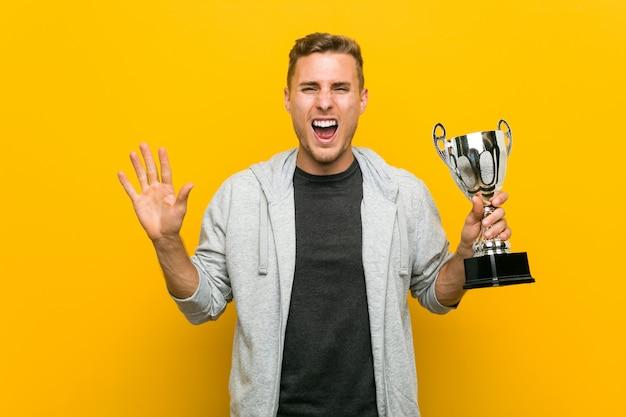 Jovem homem caucasiano segurando um troféu comemorando uma vitória