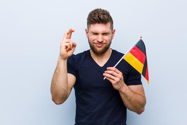 Jovem homem caucasiano segurando uma bandeira da alemanha cruzando os dedos por ter sorte