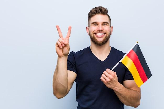 Jovem homem caucasiano segurando uma bandeira da alemanha mostrando o número dois com os dedos.