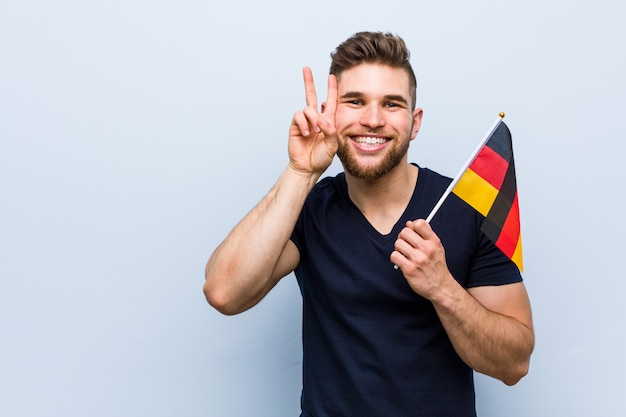 Jovem homem caucasiano segurando uma bandeira da alemanha mostrando sinal de vitória e sorrindo amplamente.