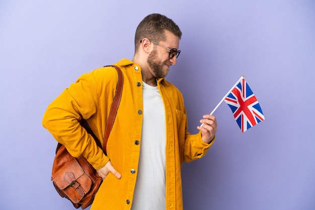 Jovem homem caucasiano segurando uma bandeira do reino unido isolada no fundo roxo, sofrendo de dor nas costas por ter feito um esforço