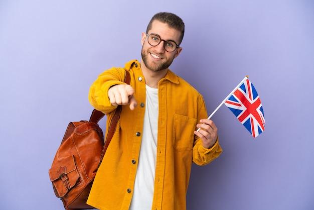 Jovem homem caucasiano segurando uma bandeira do reino unido isolada no roxo, apontando para a frente com uma expressão feliz