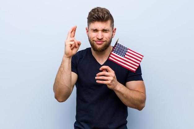 Jovem homem caucasiano segurando uma bandeira dos estados unidos, cruzando os dedos por ter sorte