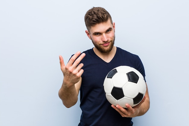 Jovem homem caucasiano segurando uma bola de futebol, apontando com o dedo para você, como se estivesse convidando para se aproximar.