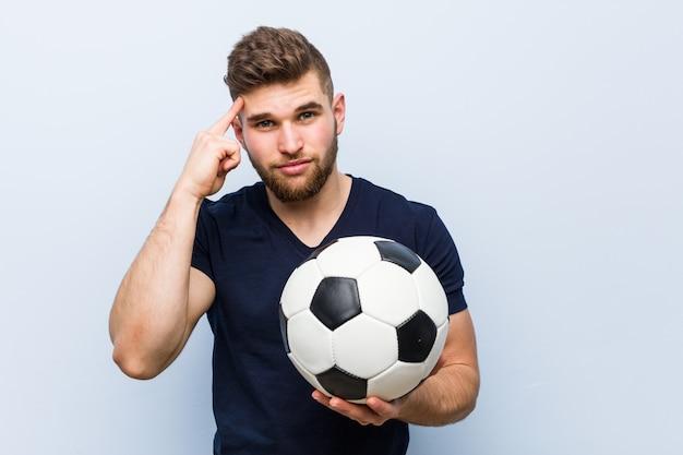 Jovem homem caucasiano segurando uma bola de futebol, apontando seu templo com o dedo, pensando, focado em uma tarefa.