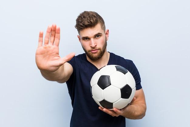 Jovem homem caucasiano segurando uma bola de futebol em pé com a mão estendida, mostrando o sinal de stop, impedindo-o.