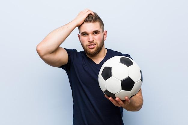 Jovem homem caucasiano segurando uma bola de futebol estar chocado, ela se lembrou de uma reunião importante.