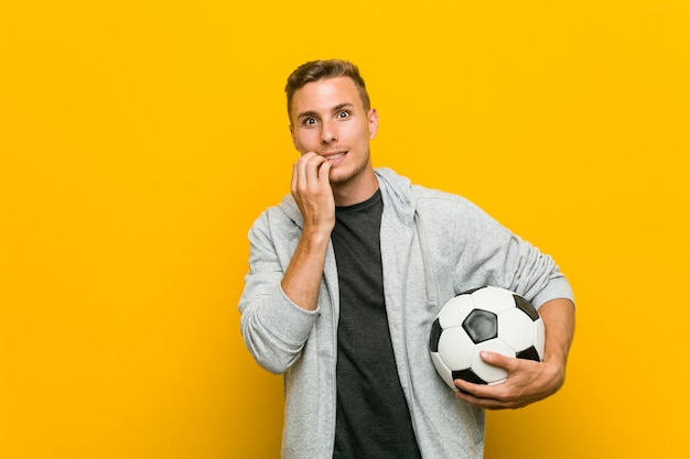 Jovem homem caucasiano segurando uma bola de futebol, roer as unhas, nervoso e muito ansioso.