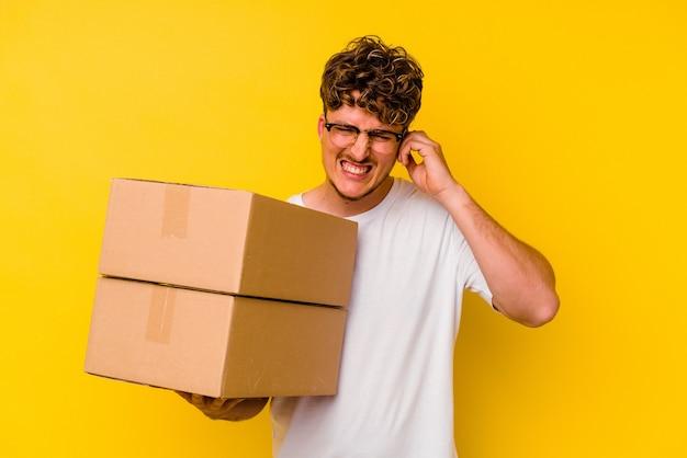 Jovem homem caucasiano segurando uma caixa de papelão isolada em um fundo amarelo, cobrindo as orelhas com as mãos.