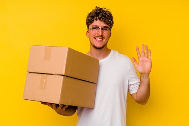 Jovem homem caucasiano segurando uma caixa de papelão isolada na parede amarela, sorrindo alegre mostrando o número cinco com os dedos.