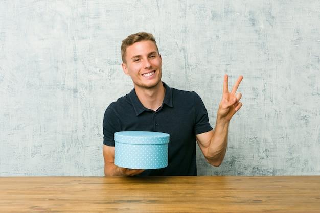Jovem homem caucasiano segurando uma caixa de presente em uma mesa alegre e despreocupada, mostrando um símbolo de paz com os dedos.