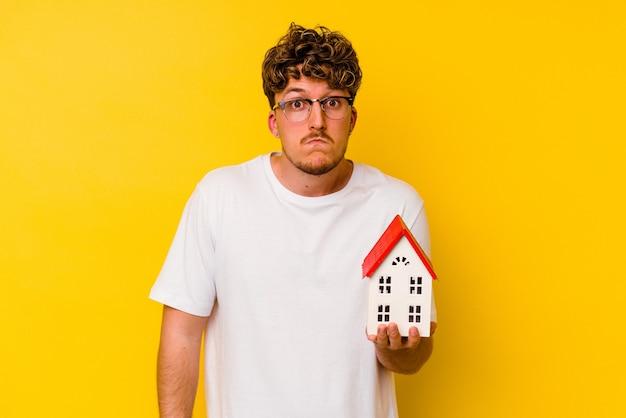 Jovem homem caucasiano segurando uma casa modelo isolada em fundo amarelo encolhe os ombros e abre os olhos confusos.