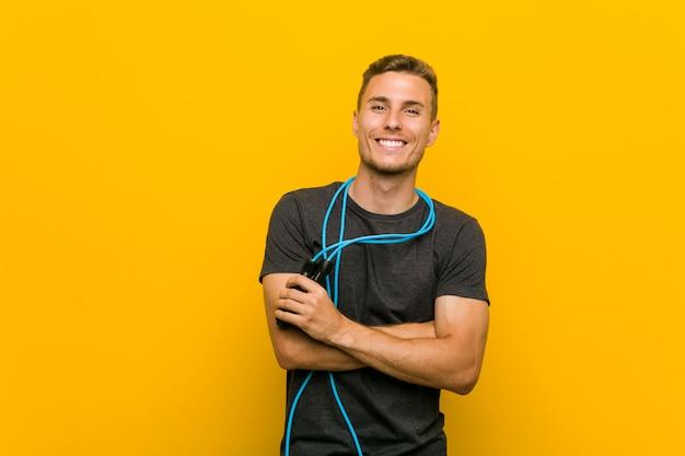 Jovem homem caucasiano segurando uma corda de pular sorrindo confiante com braços cruzados.
