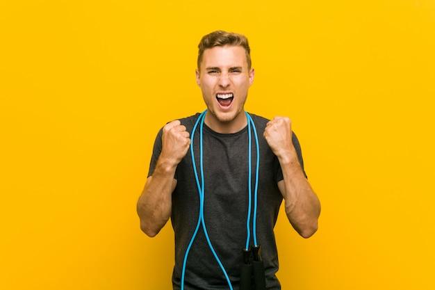 Jovem homem caucasiano segurando uma corda de pular torcendo despreocupado e animado. conceito de vitória
