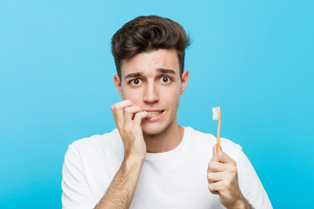 Jovem homem caucasiano segurando uma escova de dentes jovem indiana vestindo pijama e máscara de dormir isolada segurando um travesseiro roendo as unhas, nervosa e muito ansiosa. <mixto>