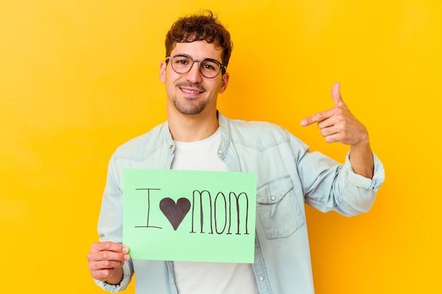Jovem homem caucasiano segurando uma folha de papel com o texto: eu amo a mãe