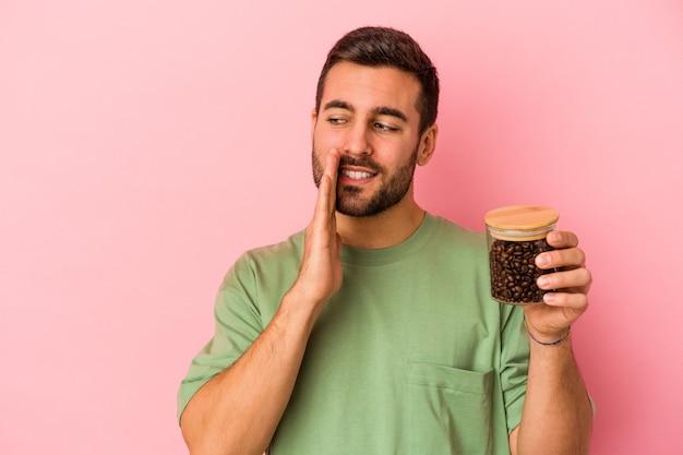 Jovem homem caucasiano segurando uma garrafa de café isolada na parede rosa está contando uma notícia secreta sobre a travagem e olhando para o lado