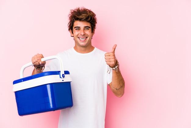 Jovem homem caucasiano segurando uma geladeira portátil, sorrindo e levantando o polegar