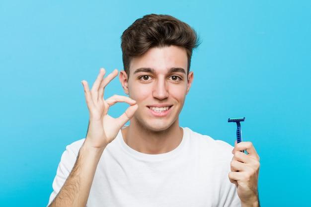 Jovem homem caucasiano segurando uma lâmina de barbear alegre e confiante mostrando o gesto ok.