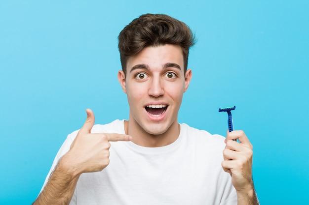 Jovem homem caucasiano segurando uma lâmina de barbear surpreendeu apontando para si mesmo, sorrindo amplamente.