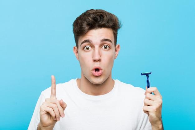 Jovem homem caucasiano segurando uma lâmina de barbear, tendo uma ótima idéia, conceito de criatividade.