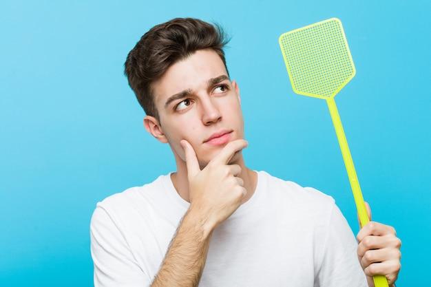 Jovem homem caucasiano segurando uma mata-moscas, olhando de soslaio com expressão duvidosa e cética.