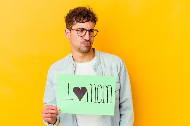 Jovem homem caucasiano segurando uma nota com o texto: eu amo a mãe. feliz dia das mães