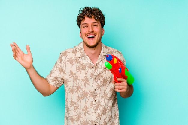 Jovem homem caucasiano segurando uma pistola de água isolada sobre fundo azul, recebendo uma agradável surpresa, animado e levantando as mãos.