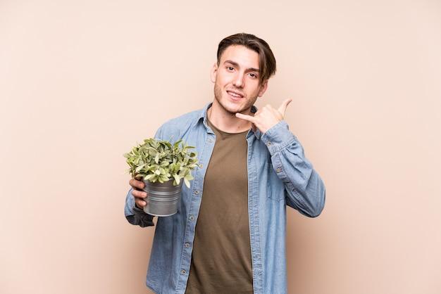 Jovem homem caucasiano segurando uma planta mostrando um gesto de chamada de telefone móvel com os dedos.