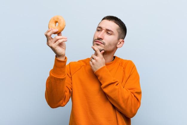 Jovem homem caucasiano segurando uma rosquinha olhando de soslaio com expressão duvidosa e cética.