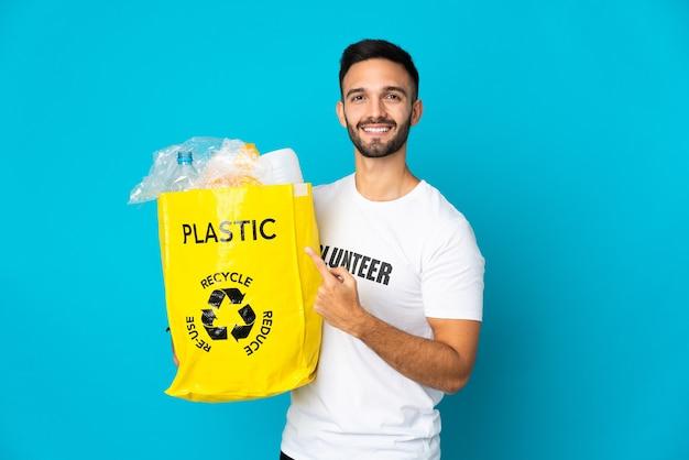 Jovem homem caucasiano segurando uma sacola cheia de garrafas plásticas para reciclar isolada em um fundo azul apontando para o lado para apresentar um produto